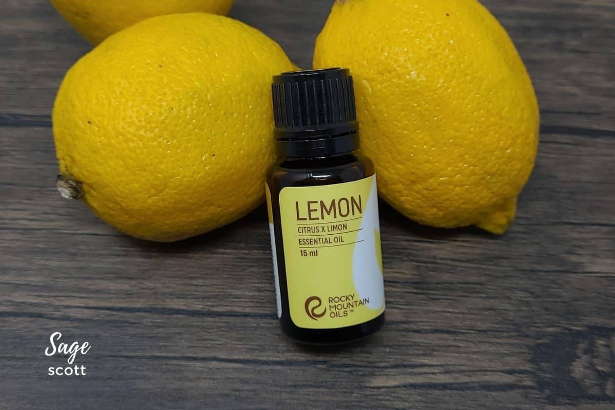 Bottle of lemon essential oil by fresh lemons