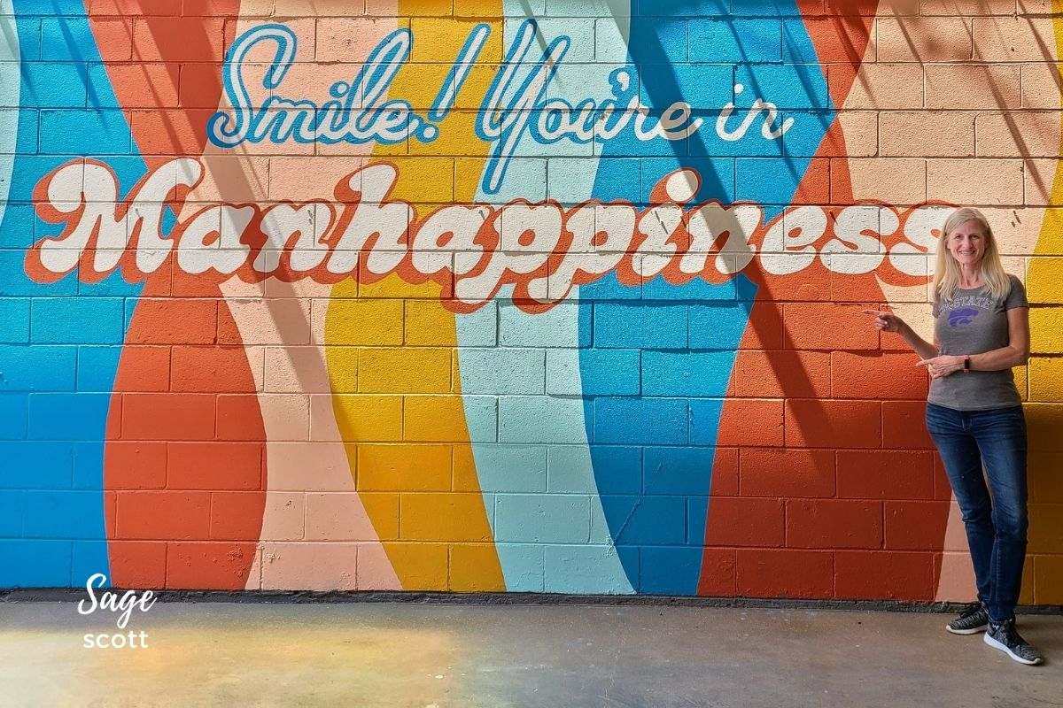 """Sage standing in front of the colorful """"Smile You're in Manhappiness"""" mural in Manhattan KS"""