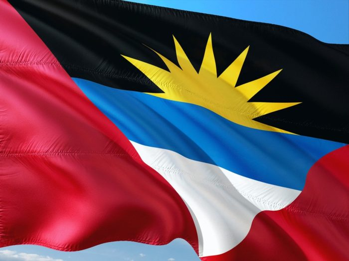 "The sun flag representing the Caribbean island nation of Antigua and Barbuda features a sun rising inside a ""V"" for victory."