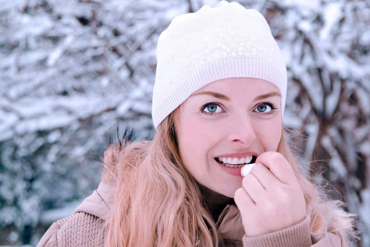 Woman Applying Chapstick in Snow
