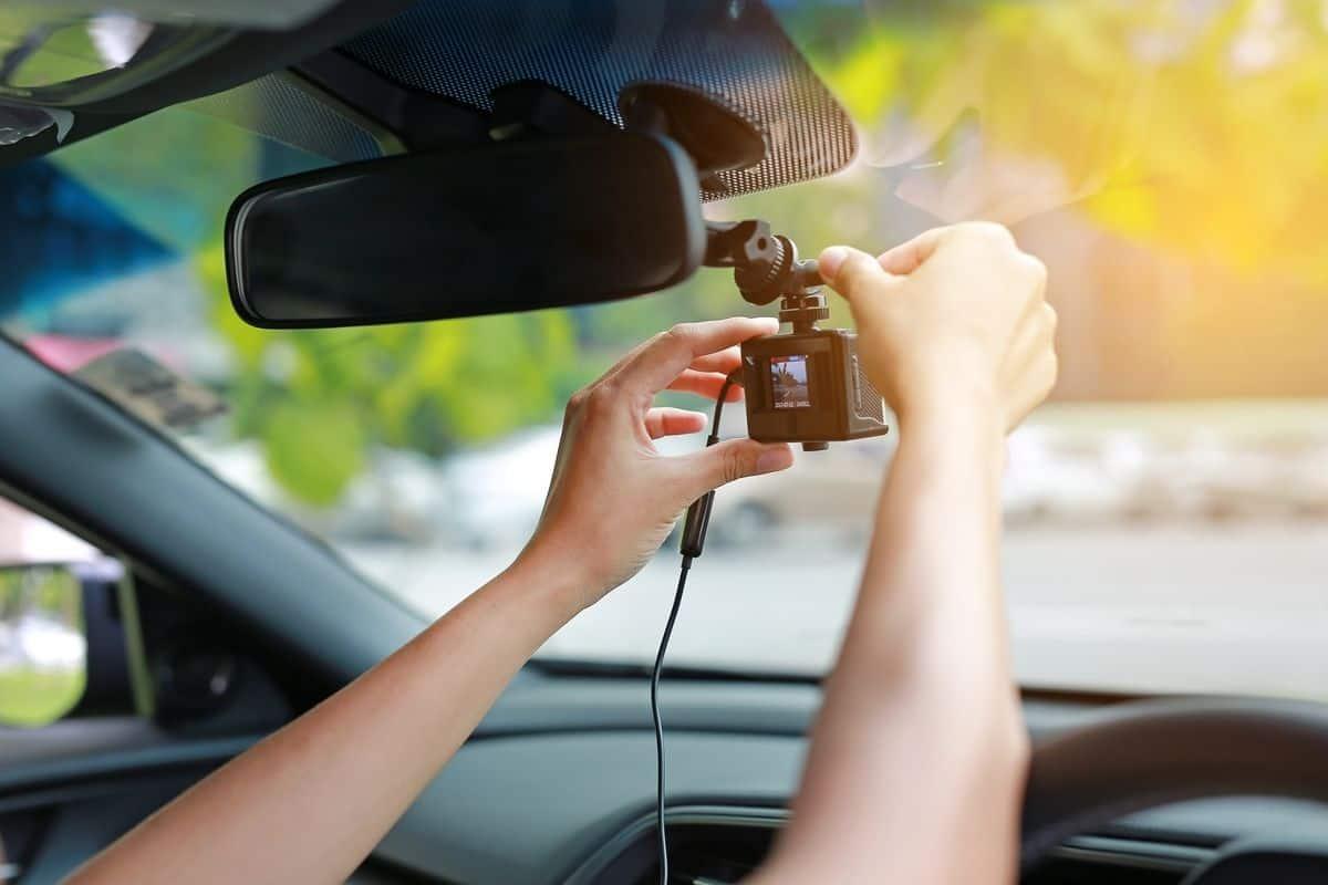 Woman installing dash cam in car