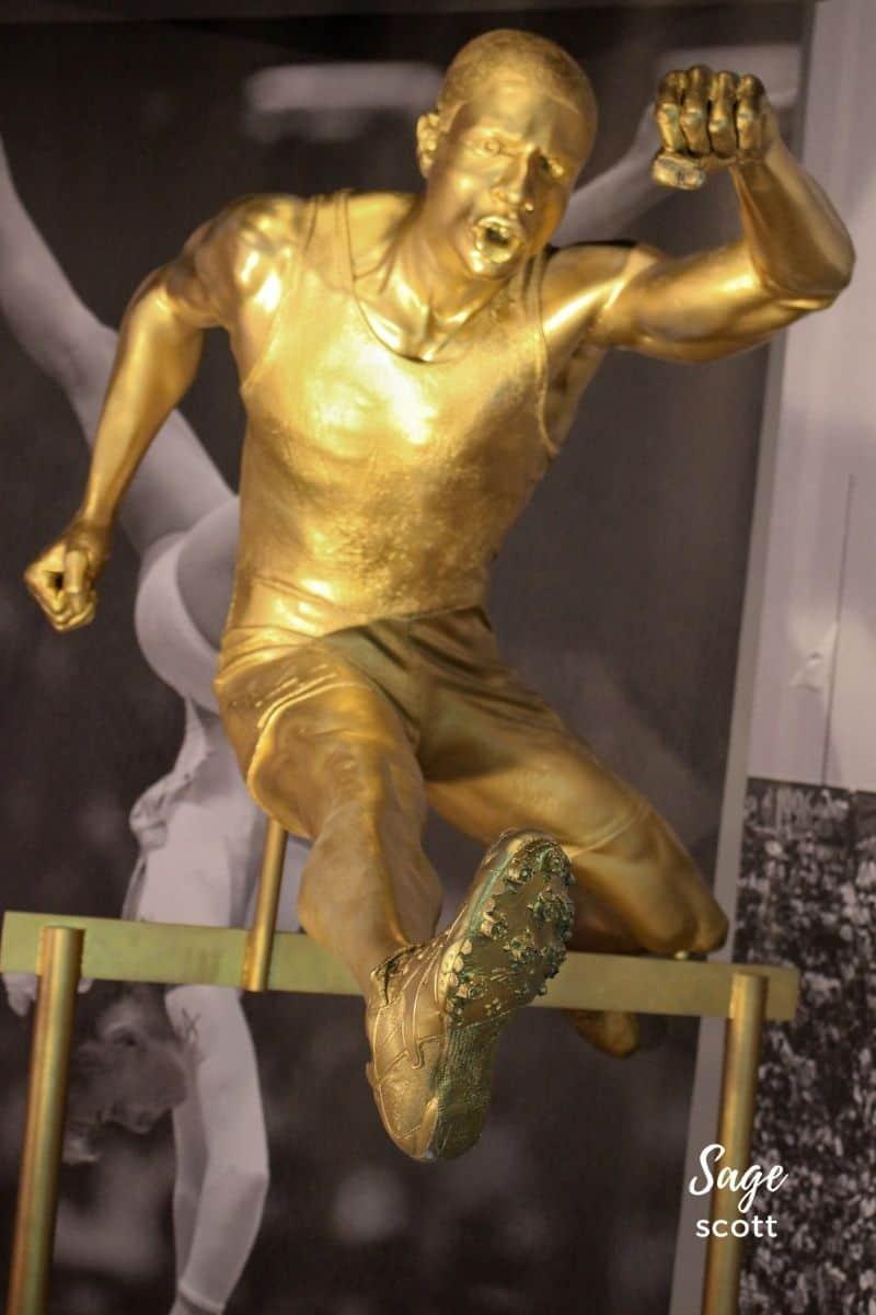 Gold sculpture of a male hurdler at the Atlanta Olympics exhibit